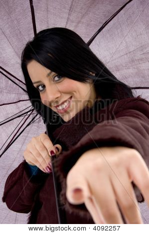 Front View Of Pointing Woman Holding Umbrella On White Background