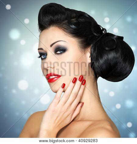 Frau mit roten Lippen, Nägel und kreative Frisur gestalten
