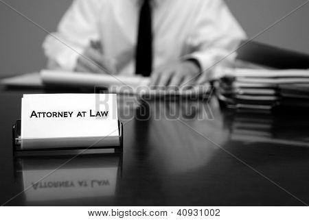 Advogado sentado na mesa, segurando a caneta com arquivos com cartão
