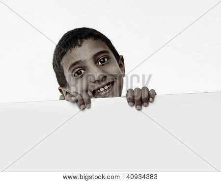 Cute little african boy behind a white board