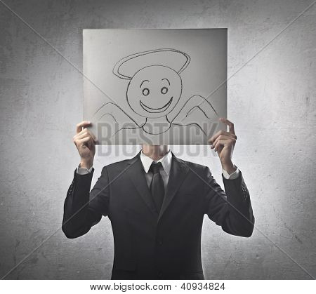 Businessman covering his face with a cardboard on which is drawn an angel face
