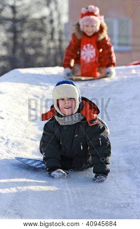 Funny kids slide down the ice slide