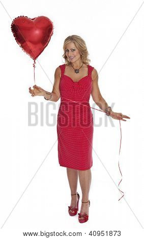 Full length photo of 40 year old woman in red dress holding heart shaped red balloon on white background.
