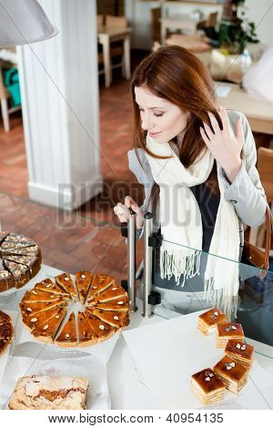 Woman in scarf looking at the bakery glass case full of different pieces of pies