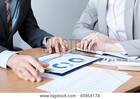 Two business people discuss meeting targets sitting at the business table with documents