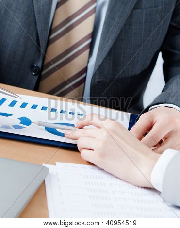 Two business people discuss current issues sitting at the business table with documents