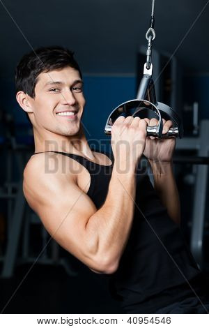 Athletic young man works out on gym equipment in fitness gym