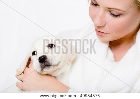 Close up of woman in white sweater looking at the white puppy of Labrador