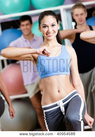 Sexy female coach exercises with her group at the gym in a fitness class helping them to loose weight