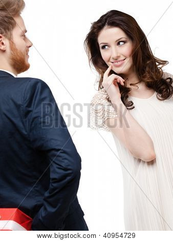 Young man hides the present behind the back from his pretty girlfriend, isolated on white