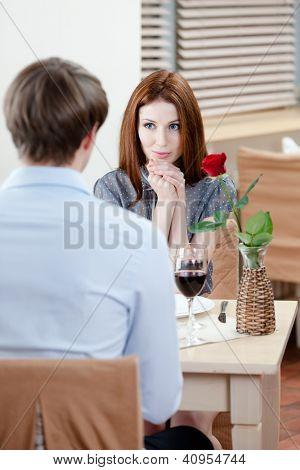 Casal está na casa de café sentado à mesa com vaso e vermelho levantou-se nele