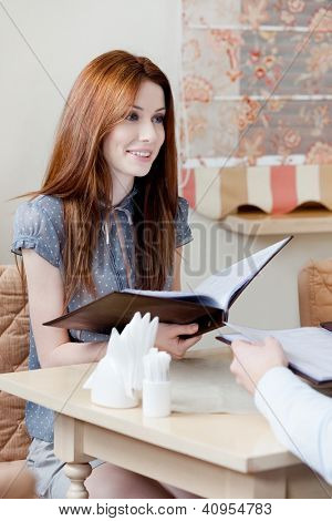 Woman hands the menu choosing a dish to make an order