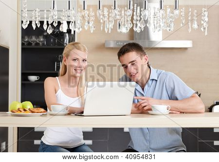 Having breakfast couple with the cup of tea surfs on the internet