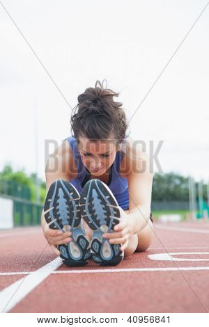 Woman stretching out on a track in a stadium