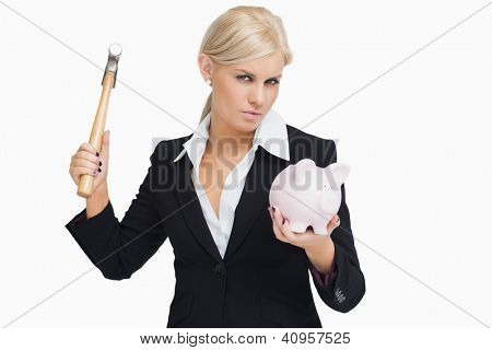 Serious businesswoman holding a hammer and a piggy-bank against white background