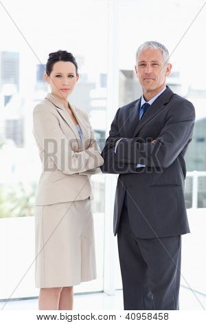 Young businesswoman standing upright in front of the window with her director