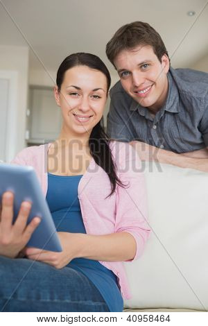 Young couple using a tablet computer and having fun on the couch