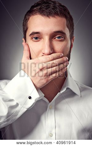 young adult man holding hand over his mouth over grey background