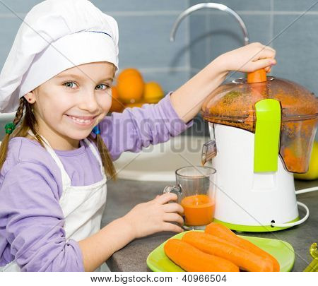 little girl making fresh carrot juice with a juice extractor