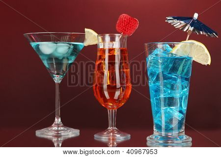 Alcoholic cocktails with ice on darck red background