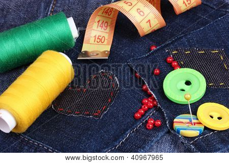 Heart-shaped patch on jeans with threads and buttons closeup