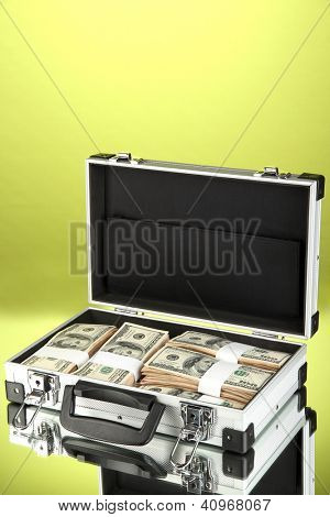 Suitcase with 100 dollar bills on green background