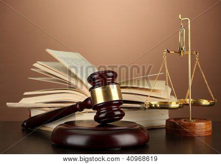 Escalas de oro de la justicia, martillo y libros sobre fondo marrón