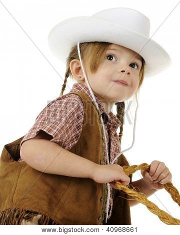 Low angle, closeup image of a preschool cowgirl with her hands on rope reigns.  On a white background.