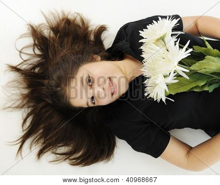 An overhead view of a pretty preteen happily resting on her back with a bouquet of flowers.
