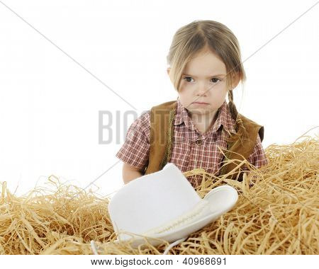 Head and shoulders of an adorable preschool cowgirl pouting behind a pile of hay.  Her hat is off, in front of her.  On a white background.
