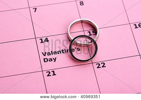Notes on the calendar (valentines day) and wedding rings, close-up