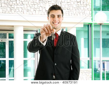 Portrait of an agent giving you the keys of your new property