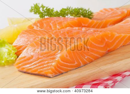 two pieces of salmon fillet on the wooden cutting board
