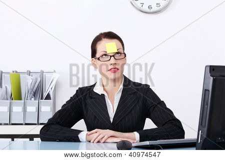 Attractive businesswoman at office with post it on her forehead.
