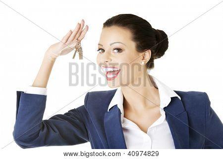 Retrato de uma feliz atrativo caucasiano empresária, agente imobiliário, segurando uma chave de casa novamente