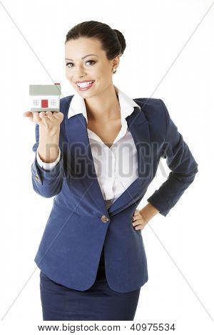 Bela mulher jovem segurando modelo de casa sobre branco - conceito de empréstimo imobiliário