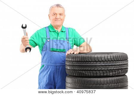 Mature mechanic standing with car tires and holding a wrench isolated on white background