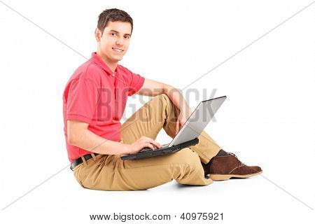 Young man sitting on the floor and working on a laptop isolated on white background
