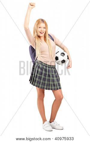 Full length portrait of an euphoric female student with backpack holding a soccer ball isolated on white background