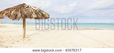 Beach umbrella on exotic caribbean plage. Travel destination background.