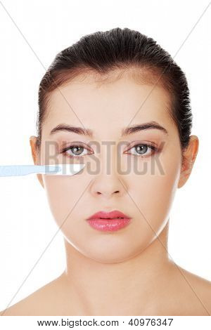 Cosmetic surgery concept. Female face in background of scalpel.