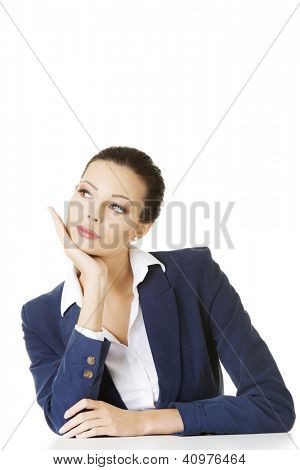 Pretty businesswoman sitting at the desk and thinking, isolated on white