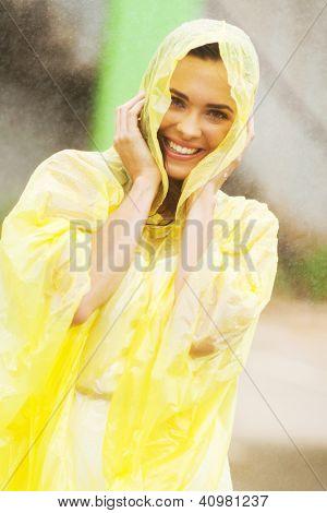 pretty woman dress in raincoat having fun in the rain