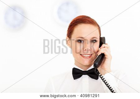 pretty young receptionist working at hotel reception