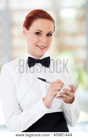 pretty waitress taking orders in restaurant