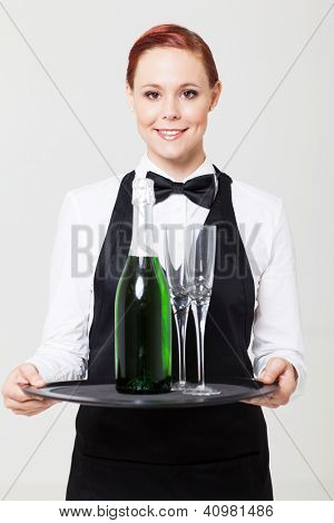 pretty young waitress holding tray with champagne and glass