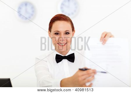 friendly hotel receptionist giving form for signing