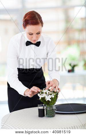 elegant young waitress setting up restaurant table