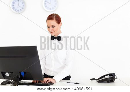 young receptionist working at hotel reception