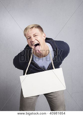 Naughty provocative man holding white blank signboard with space for text isolated on grey background.